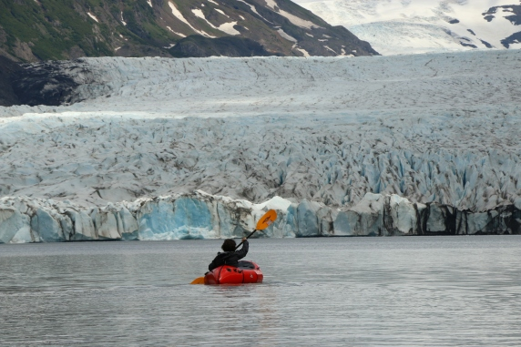 Alayne paddles to the towering face of Grewingk Glacier, AK